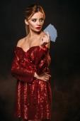 vonzó lány, a gazdaság, kártya és látszó el elszigetelt fekete piros fényes ruha