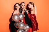 Fotografie lächelnde attraktive Girls in stilvolle Party-Kleidung hält Bündel von grauen Ballons isoliert auf orange