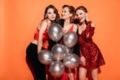 Fotografie attraktive Girls Lachen in stilvolle Party-Kleidung hält Bündel von grauen Ballons isoliert auf orange
