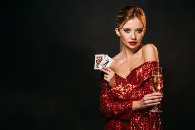 attractive girl in red shiny dress holding joker and queen of hearts cards isolated on black, looking at camera