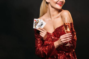 cropped image of girl in red shiny dress holding joker and queen of hearts cards isolated on black