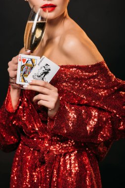 cropped image of girl in red shiny dress holding joker and queen of hearts cards, drinking champagne isolated on black