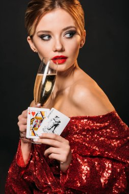 attractive girl in red shiny dress holding joker and queen of hearts cards, drinking champagne isolated on black