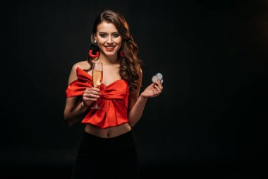 smiling beautiful brown haired girl in red corset holding glass of champagne and casino chips isolated on black