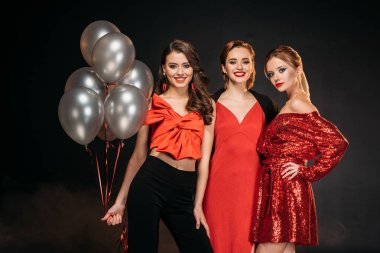 smiling attractive girls in red clothes holding bundle of grey balloons isolated on black