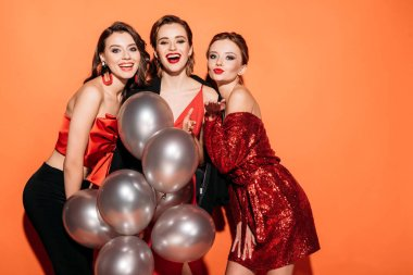 laughing beautiful girls in stylish party clothes holding bundle of grey balloons and looking at camera isolated on orange
