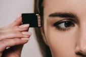 oříznutý pohled mikročip v blízkosti oka v rukou ženy