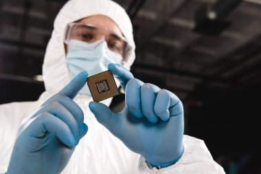 selective focus of microchip in hands of scientist wearing latex gloves