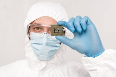 selective focus of scientist in googles holding microchip in hand isolated on grey