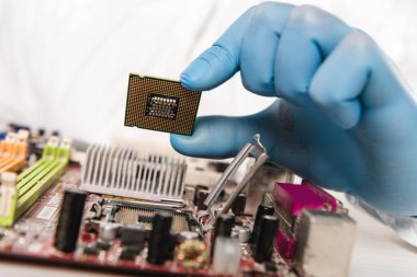 cropped view of microchip in hand of scientist near motherboard