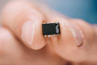 selective focus man showing black, metallic microchip