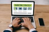 Fotografie oříznutý pohled podnikatel psaní na notebooku s ikonami marketingové strategie