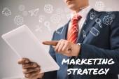 oříznutý pohled podnikatel pomocí digitálních tabletu ikonami marketingové strategie