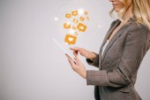 Photo cropped view on businesswoman in suit touching digital tablet with multimedia icons isolated on grey