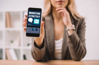 cropped view of businesswoman presenting smartphone with marketing strategy
