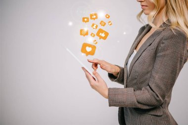 cropped view on businesswoman in suit touching digital tablet with multimedia icons isolated on grey