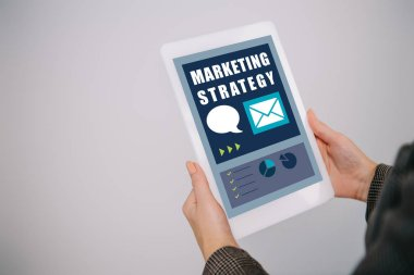 cropped view on businesswoman using digital tablet with marketing strategy isolated on grey