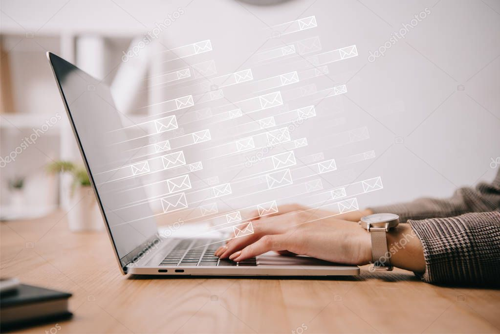 cropped view of businesswoman working and typing on laptop with sending e-mails icons