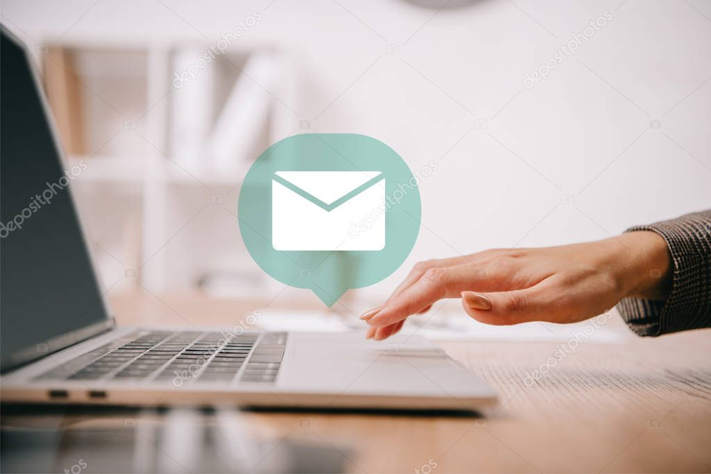 cropped view of businesswoman typing on laptop at workplace with email icon