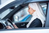 boční pohled na krásné mladé muslimské ženy řídí auto