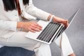 oříznuté záběr mladé ženy ve stylovém bílém obleku přenosném počítači doma