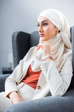beautiful pensive young muslim woman sitting in chair and looking away
