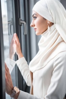 Side view of young muslim woman looking at window stock vector