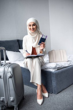 Beautiful young muslim woman holding passport with boarding pass and smiling at camera at home stock vector