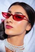 Detailní portrét krásná mladá žena v červené brýle při pohledu na fotoaparát