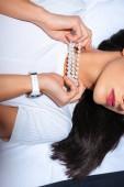 Fotografie cropped shot of elegant brunette girl in pearl necklace lying on bed