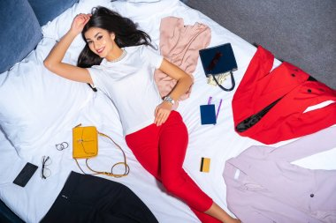 beautiful girl smiling at camera while lying on bed with fashionable clothes, handbags with money, credit card and passport with ticket