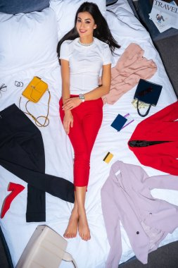 top view of beautiful girl smiling at camera while lying on bed with fashionable clothes, passport, credit card and travel newspaper