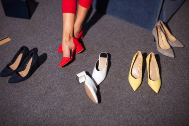 low section of girl in stylish red shoes and various fashionable footwear on carpet