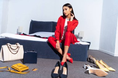 beautiful young woman in stylish red suit sitting on bed and looking at camera, various fashionable shoes and handbags on floor