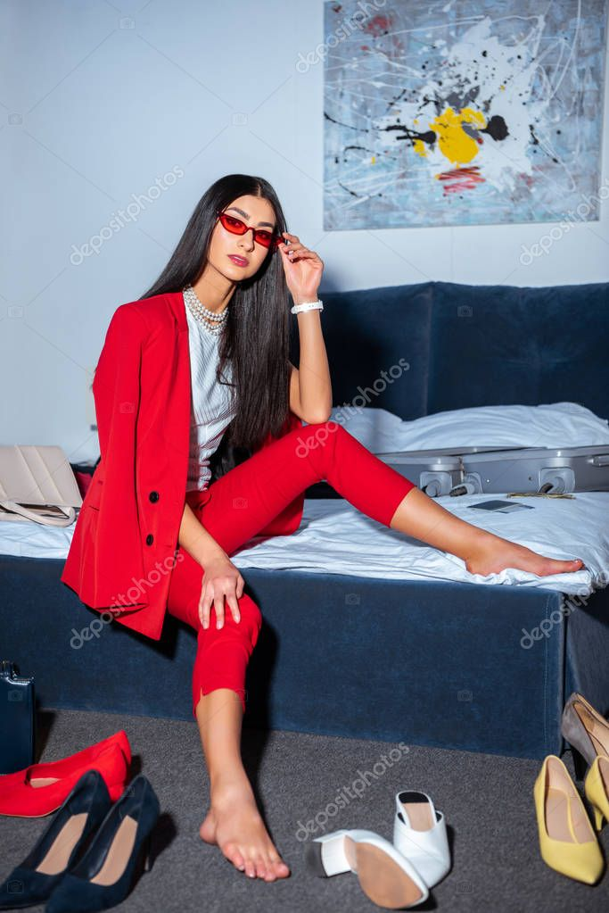 Beautiful young woman in fashionable red suit and sunglasses sitting on bed and looking at camera stock vector
