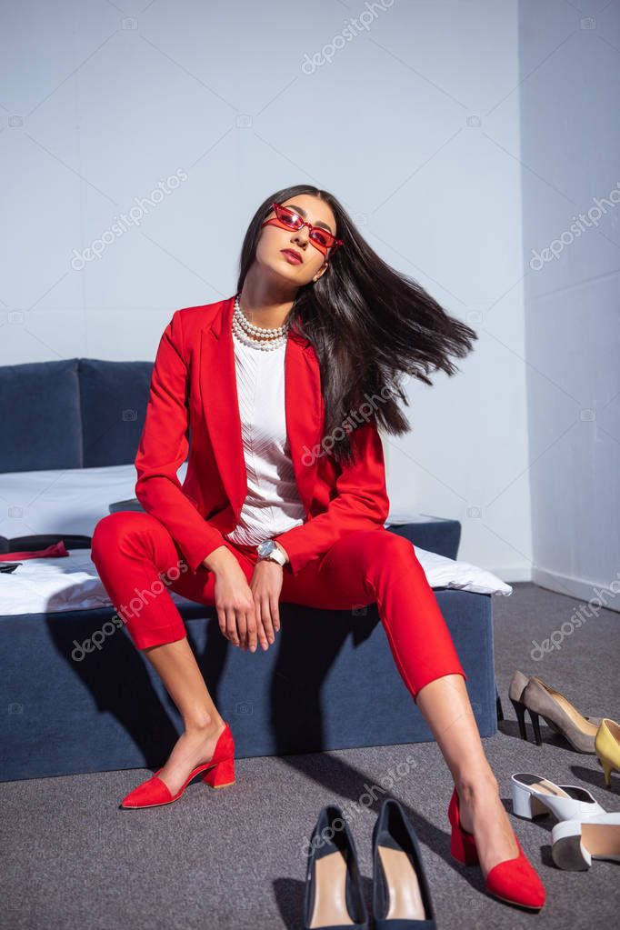 Beautiful young woman in fashionable red suit and sunglasses sitting on bed stock vector