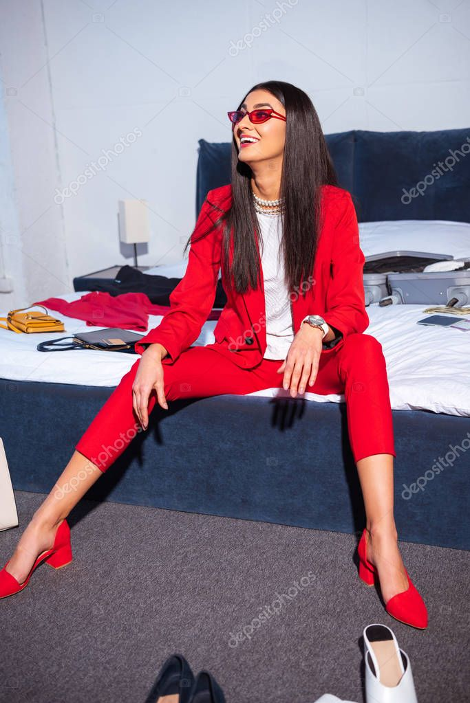 Beautiful smiling young woman in stylish red suit and sunglasses sitting on bed stock vector