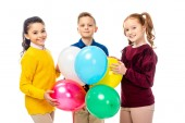 smiling boy and schoolgirls holding colorful balloons and looking at camera isolated on white