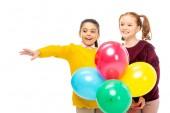 Fotografia studentesse allegri che tiene i palloni variopinti isolati su bianco
