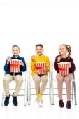 veselé děti sedí na židlích, držel prokládané kbelíky a jíst popcorn izolované na bílém