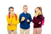 roztomilý školáci s batohy jedl jablka a při pohledu na fotoaparát izolované na bílém