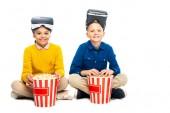 Lächelnde Kinder mit Virtual-Reality-Headsets auf Köpfen, die gestreifte Popcorn-Eimer in der Hand halten und isoliert auf weiße Kameras schauen