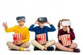 ohromen dětí s virtuální realita sluchátka na hlavě drží prokládané kbelíky a jíst popcorn izolované na bílém