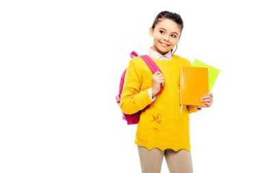 adorable child with backpack holding books and smiling isolated on white