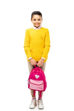 adorable child holding backpack and smiling at camera isolated on white