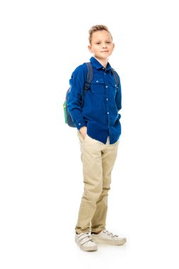 cute schoolboy in blue shirt standing with hands in pockets isolated on white