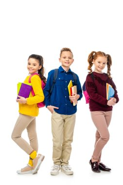 cute schoolchildren with backpacks holding books and smiling isolated on white