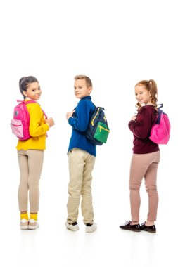 cute schoolchildren showing backpacks while looking at camera isolated on white