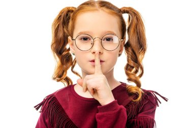 adorable child in glasses showing hush gesture and looking at camera isolated on white