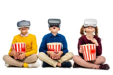 Amazed children with virtual reality headsets on heads holding striped buckets and eating popcorn isolated on white stock vector